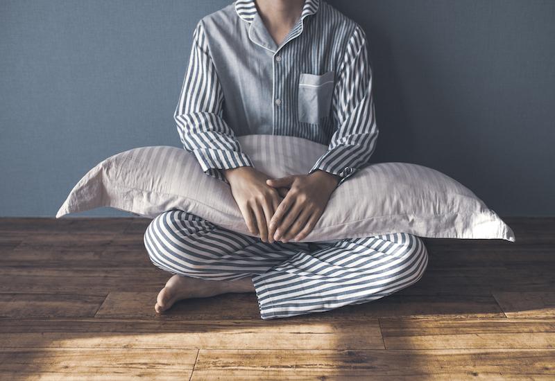 不眠・枕を持って座る男性
