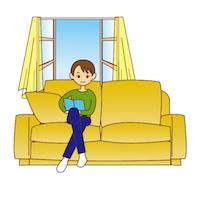 ソファーで本を読む男性
