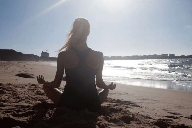 砂浜でヨガをする女性